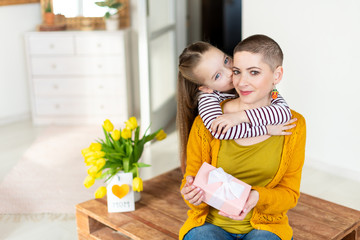 Happy Mother's Day or Birthday Background. Adorable young girl surprising her mom, young cancer patient, with bouquet with present. Family celebration concept.