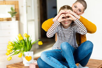 Mother and daughter looking through heart shaped love symbol hand gesture. Family, love, togetherness concept.
