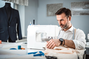 Tailor working with sewing machine at fashion design workshop