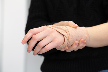 Girl holding with hand her bandaged wrist after an accident
