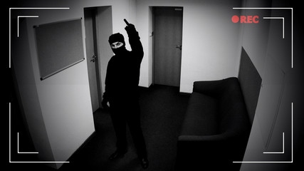 Dangerous criminal in balaclava showing middle finger at surveillance camera - fototapety na wymiar