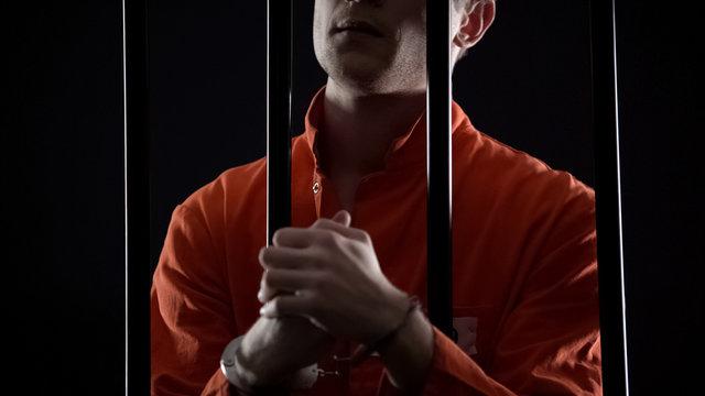 Handcuffed prisoner eagerly waiting for appeal court verdict, feeling nervous