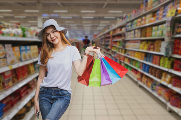 Young woman with shopping bags walking and shopping in supermarkets, Woman lifestyle concept