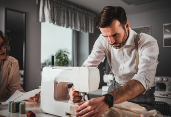 Professional tailors during work on project using sewing machine at fashion design studio