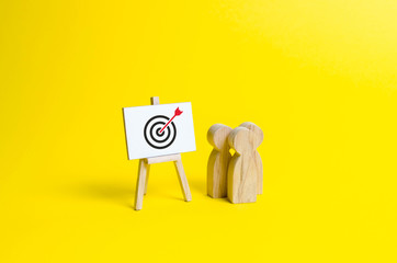 people are standing near the canvas with arrow symbol in the center of the target. Targeting and marketing, advertising. Presentation of information on income and expenses, achievement of goals