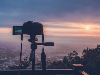 photography concept from camera set on tripod take photos and video of sunrise with city at viewpoint, Chiang Mai, Thailand
