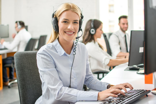 Smiling customer support worker woman with headset working on computer in call center