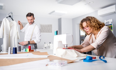 Professional tailors during work on project in fashion design studio, using sewing equipment