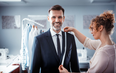 Professional tailor using tape to measuring client for sewing suit at fashion design studio