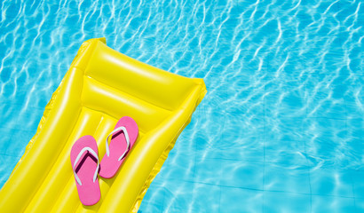 Beach summer holiday background. Inflatable air mattress, flip flops on swimming pool. Yellow lilo and summertime accessories on poolside. Top view and copy space