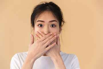 Image of silent chinese woman wearing basic t-shirt covering her mouth with hands