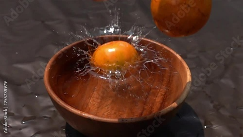 Fototapete Oranges falling into the water in wooden bowl on dark background in Slow Motion