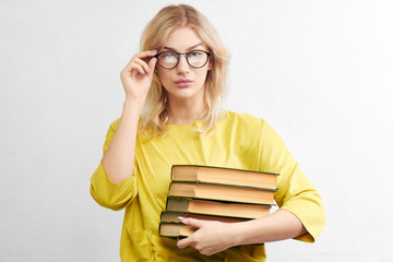 Sexy blonde woman teacher in round glasses with books on a white background in the studio. Education and science concept
