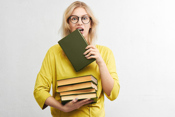 A smart blonde with glasses nibbles a book on a white background alone. Concept science and education