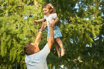 playing father and daughter. dad throws up the child