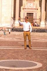 A businessman on a square taking a selfie