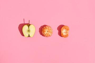 Food design. Composition of half of apple, peeled mandarin and half of peeled mandarin on pink coral background