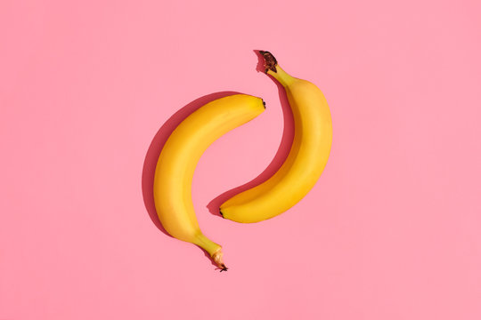 Composition of a pair of bananas lying next to a pink background in the center of the image, top view