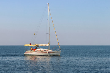 White sailing yacht with lowered sails in the sea