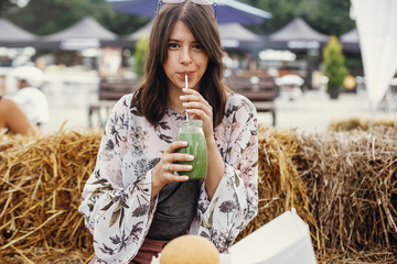 Stylish hipster boho girl drinking smoothie in glass jar with delicious vegan burger on wooden table at street food festival. Happy woman with healthy drink in summer street. Zero waste