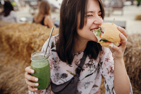 Stylish hipster girl in sunglasses eating delicious vegan burger and holding smoothie in glass jar in hands at street food festival. Happy boho woman biting burger with drink in summer street