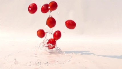 Fototapete - Cherry tomatoes falling on the white floor in Slow Motion