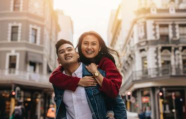 Asian couple piggybacking on city street