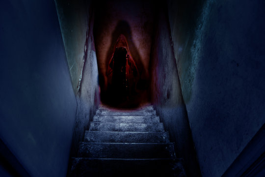 Dark figure in a red cape with a hood on the old concrete stairs in the descent to the basement.