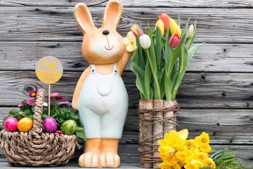Fröhlicher Osterhase mit Narzissen und Tulpen als Dekoration zu Ostern