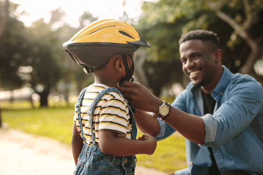 Father helping his son to wear a cycling helmet