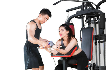 Asian woman uses exercise machine with her trainer