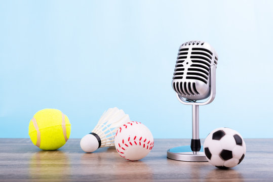 Concept sports commentator : The retro microphone put on the wooden table with football or soccer , tennis ball , baseball and shuttlecock isolated on blue background