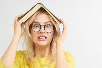 Educational concept. European student girl in round glasses and yellow clothes holds a textbook on head, stress from studying. Portrait on a white studio background
