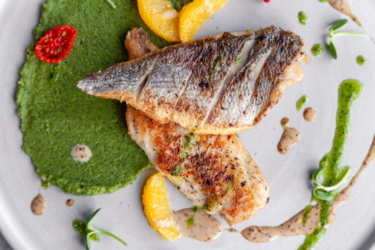 Closeup fried sea bass fillet with green pea puree, tomatoes, sauce, orange slices. Concept professional photography, photosession new menu, profession food stylist, flat-lay, freelancer