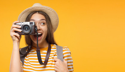 Tourism concept. Horizontal banner of excited young woman tourist holding photo camera, isolated on yellow background with copy space