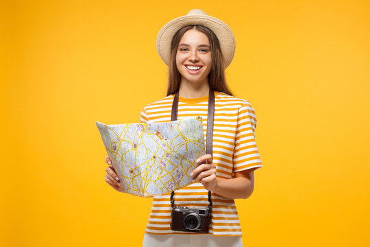 Young cheerful female tourist holding oldschool paper map, isolated on yellow background