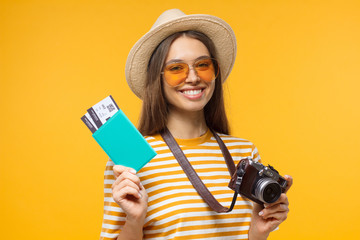 Excited cheerful young tourist girl holding passport with tickets and camera, isolated on yellow background Wall mural