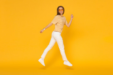 Happy young woman jumping like she walking in the air, isolated on yellow background