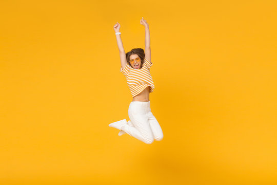 Successful young female acts like winner, jumping high in the air with hands up, isolated on yellow background