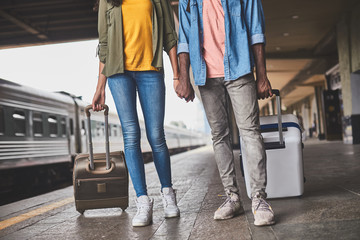 Wall Mural - Young man and woman are walking at railway station