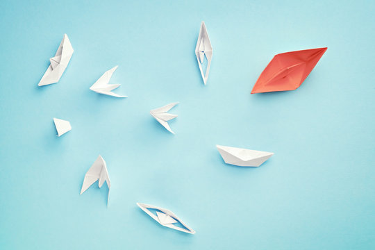 Unsuccessful leadership concept. Red paper boat and a lot of sinking ships