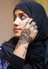 An Iraqi woman shows hand decorated with henna as she poses for a photo in Basra