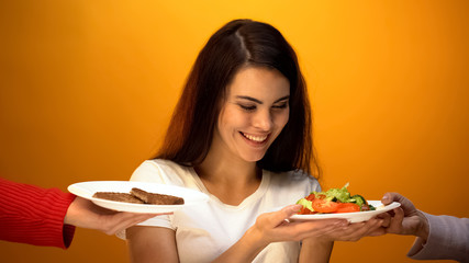 Vegan girl choosing fresh green salad instead of meat, vitamins in vegetables