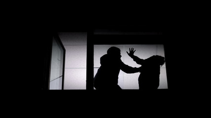 Silhouette of couple arguing, man beating helpless woman, domestic violence