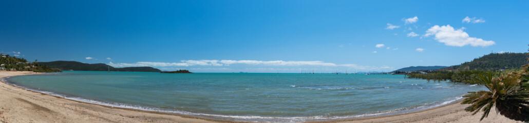 Panorama eines Badestrand in einer Bucht mit leicht bewölktem blauen Himmel