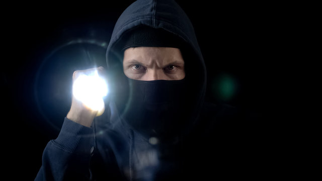 Lawbreaker in balaclava mask flashing torch, searching for important information