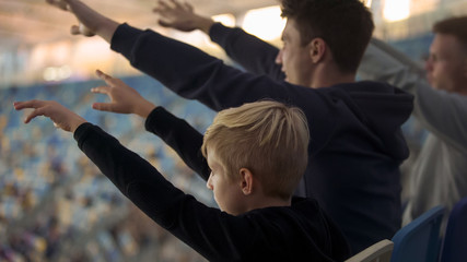Male supporters and boy putting hands in air, cheering football team at stadium