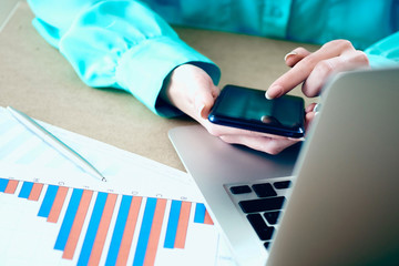 Female hands holds smartphone pointing finger touchscreen phone, laptop financial graphs on background.