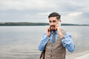 A good deal! Bearded businessman speaks by phone and laughs.View of a Young attractive business man  using smartphone. Smiling formal dressed businessman talking on cell phone with customers