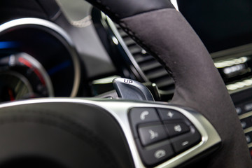 A close-up view of a part of the interior of a modern luxury car with a view of the gearshift paddles made of chrome with the inscription Up with black trim elements of the passenger compartment